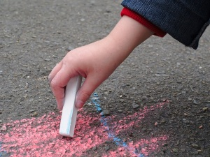 Child drawing with sidewalk chalk.