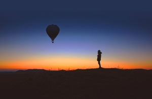 A lone person observes an hot air balloon at sunrise