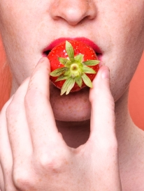 close up of woman mouth eating strawberry