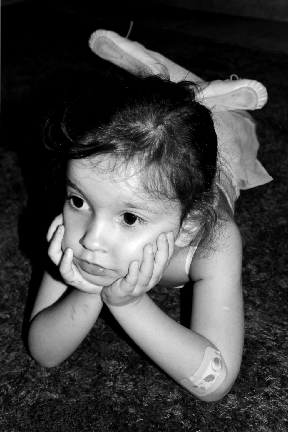 Black & white close-up image of a thoughtful young ballerina with a band aid on the elbow