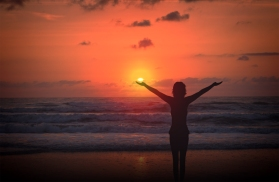 Celebrating life - A woman raises her arms at sunset on a desert