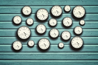 Many clocks in a blue wooden background