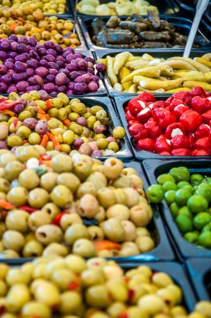 Different marinated olives on market
