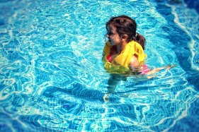 Little Girl Learning To Swim with Life Vest