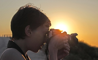 Child taking a picture with DSLR camera at sunset