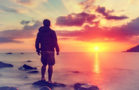 Young Man Watching the Sunrise at Rocky Beach